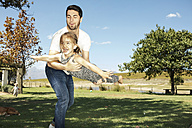 Father playing with daughter in garden - ZEF13947