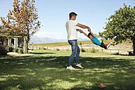 Father playing with son in garden - ZEF13950