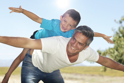 Father playing with son outdoors - ZEF13953