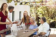 Happy family setting table outside for lunch - ZEF13962