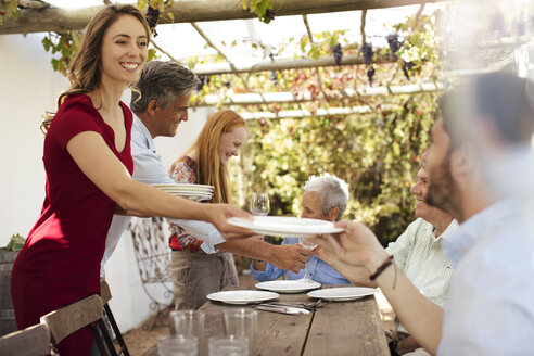 Happy family setting table outside for lunch - ZEF13965