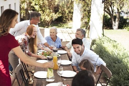 Happy family preparing lunch on garden table - ZEF13968