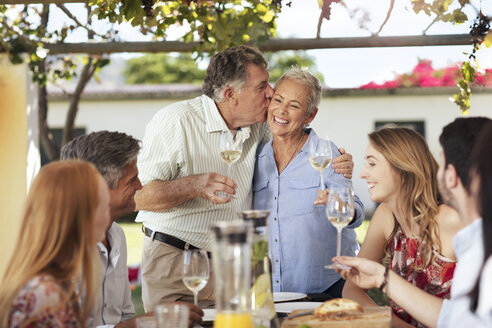 Happy senior couple with family having lunch together outside - ZEF13974
