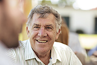 Smiling senior man socializing on a garden party - ZEF13980
