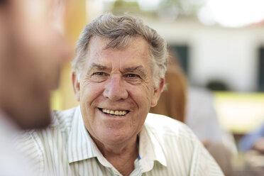 Smiling senior man socializing on a garden party - ZEF13980