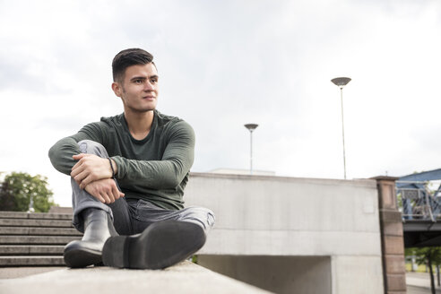 Young man sitting on wall in the city - MIDF00846