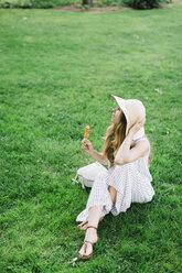 Woman sitting on meadow earing popsicle - JPF00214