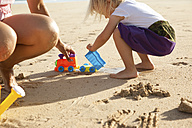 Spain, Fuerteventura, mother and daughter playing on the beach - MFRF00868