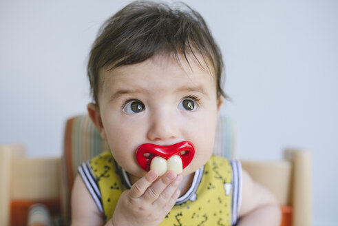 Portrait of baby girl sucking a pacifier with false teeth and mouth - GEMF01684