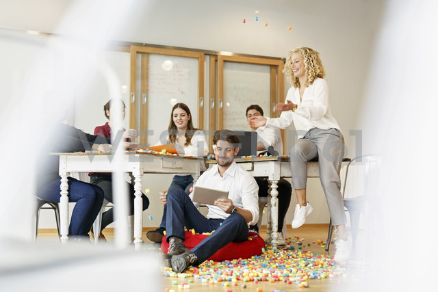 Creative professionals meeting in office surrounded by colorful polystyrene parts - PESF00634
