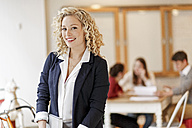 Portrait of confident businesswoman with a meeting in background - PESF00640
