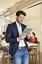 Smiling businessman using tablet in office with a meeting in background - PESF00649