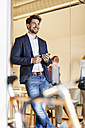 Smiling businessman with cell phone in office - PESF00655