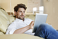 Smiling man in office using tablet in bean bag - PESF00673