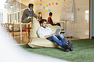 Man in office using tablet in bean bag with meeting in background - PESF00676
