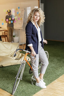 Portrait of woman with bicycle in office - PESF00685
