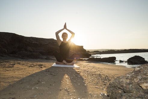 Greece, Crete, woman practicing yoga on the beach at sunset - CHPF00405