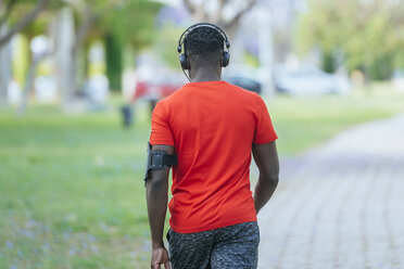 Back view of walking man in sportswear listening  music with headphones - KIJF01565