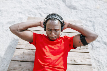 Man doing sit-ups listening music with headphones - KIJF01571