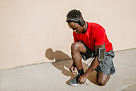 Man in sportswear tying his shoes while listening music with headphones - KIJF01574