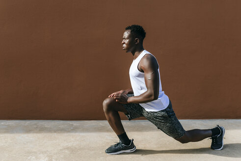Young man doing stretching exercises against brown wall - KIJF01580