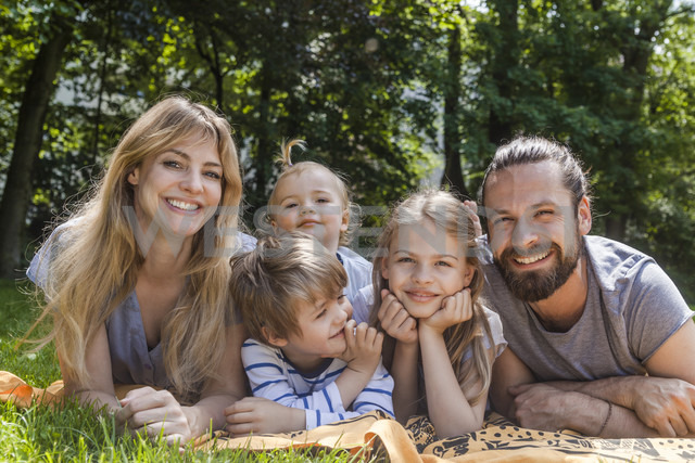 Portrait of happy family lying on meadow - TCF05436