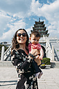 South Korea, Seoul, woman holding a baby girl in front of the National Folk Museum of Korea, inside Gyeongbokgung Palace - GEMF01691