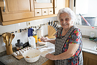 Portrait of smiling senior woman preparing meatballs in the kitchen - RAEF01890