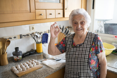 Portrait of smiling senior woman showing ok sign in the kitchen - RAEF01893