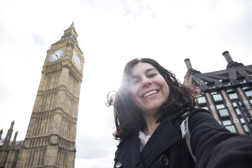 UK, London, happy woman taking selfie in front of Big Ben - ABZF02103