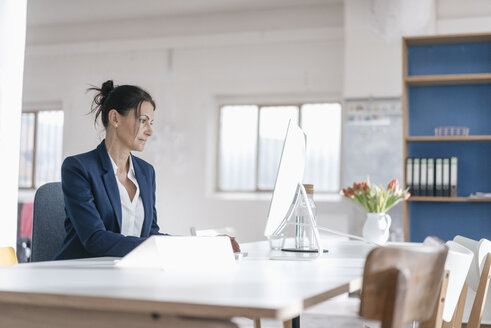 Businesswoman working at desk in a loft - JOSF01158