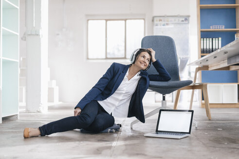 Smiling businesswoman sitting on the floor in a loft listening music with headphones - JOSF01167