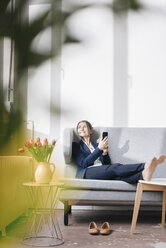 Businesswoman sitting on couch in a loft looking out of the window - JOSF01170