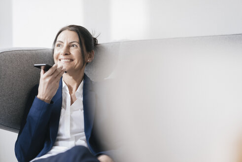 Portrait of smiling businesswoman sitting on couch using cell phone - JOSF01173
