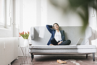 Businesswoman relaxing on couch in a loft - JOSF01176