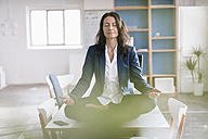 Businesswoman doing yoga exercise on desk in a loft - JOSF01182