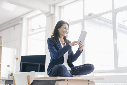 Businesswoman sitting on desk in a loft using tablet - JOSF01185