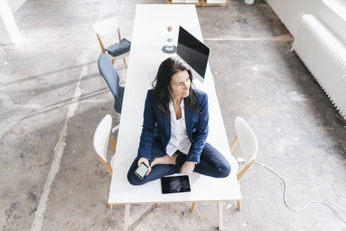 Pensive businesswoman sitting on desk in a loft with electronic devices - JOSF01188