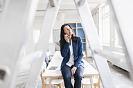 Businesswoman on the phone sitting on desk in a loft - JOSF01191