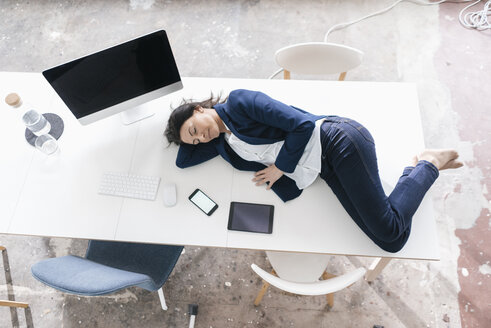 Businesswoman sleeping on desk in the office - JOSF01194