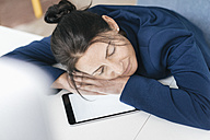 Overworked woman sleeping on tablet in office - JOSF01212