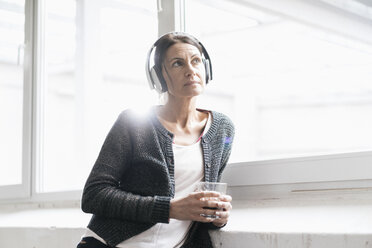 Portrait of woman in a loft listening music with headphones - JOSF01215