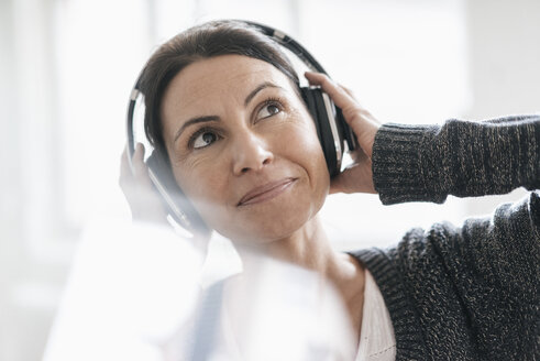 Portrait of smiling woman listening music with headphones - JOSF01218