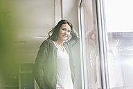 Portrait of smiling woman standing besides window in a loft - JOSF01221
