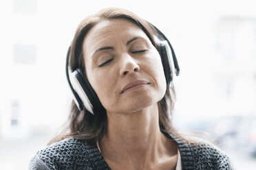 Portrait of woman with eyes closed listening music with headphones - JOSF01227