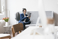 Businesswoman sitting on couch in a loft using tablet and headphones - JOSF01233