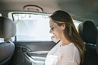 Woman traveling in car on the back seat - KIJF01587