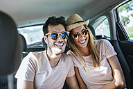 Couple laughing in the back seat of a car - KIJF01590