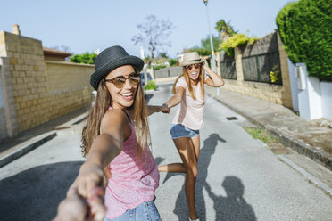 Happy friends holding hands on the street - KIJF01599