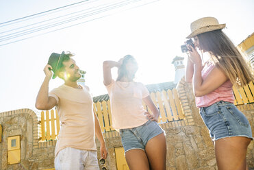 Woman taking a picture of couple on the street - KIJF01605